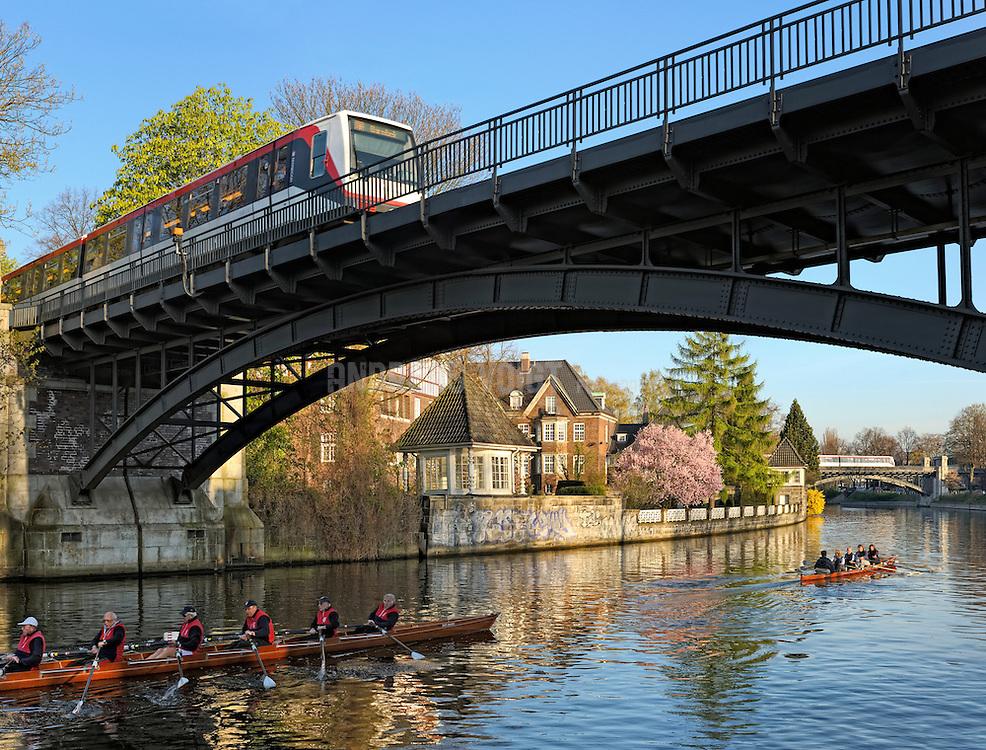 Ruderboote auf dem Alsterlauf vor dem Kloster St. Johannis in Hamburg Eppendorf beim morgenlichen Training. U-Bahnen queren die Stahlbrücken.