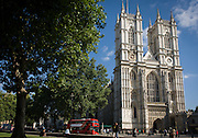 The tall western facade of London's Westminster Abbey with a new generation red London Routemaster double-decker bus passing-by.