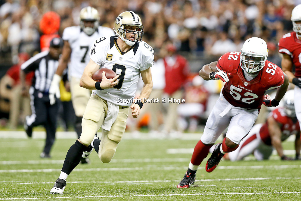 Sep 22, 2013; New Orleans, LA, USA; New Orleans Saints quarterback Drew Brees (9) runs as Arizona Cardinals inside linebacker Jasper Brinkley (52) pursues during the second half of a game at Mercedes-Benz Superdome. The Saints defeated the Cardinals 31-7. Mandatory Credit: Derick E. Hingle-USA TODAY Sports