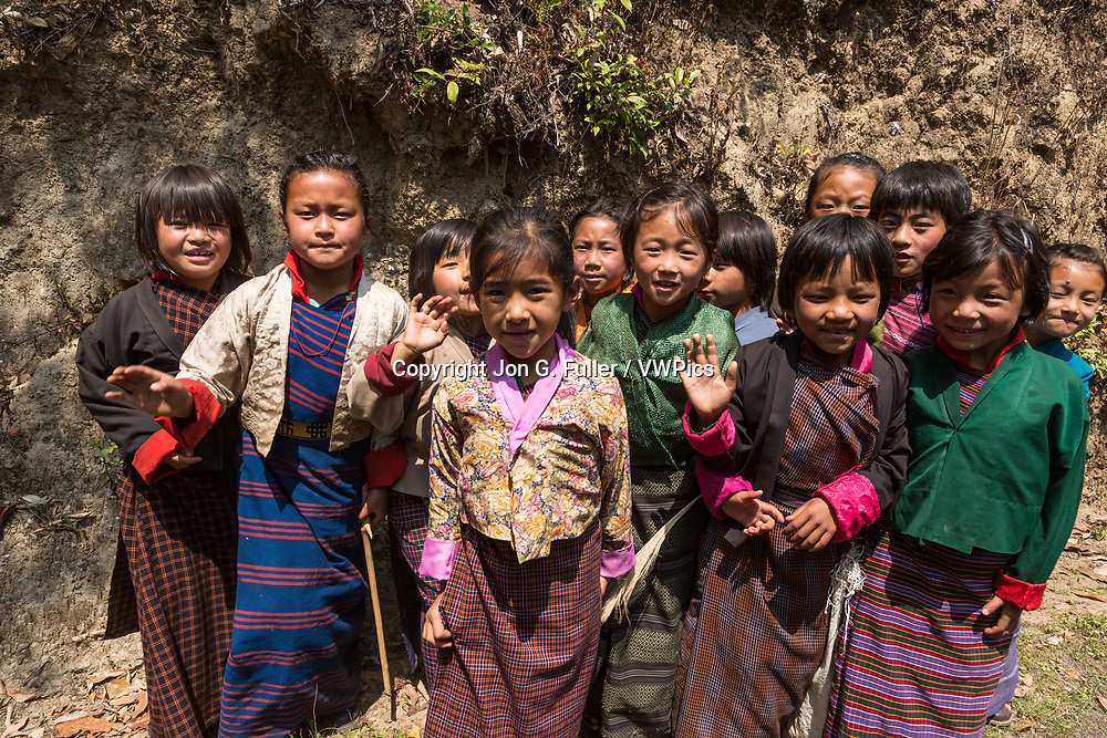 Young schoolgirls in traditional kira skirts and tego jackets pose for their picture by the road in Talo, Bhutan.