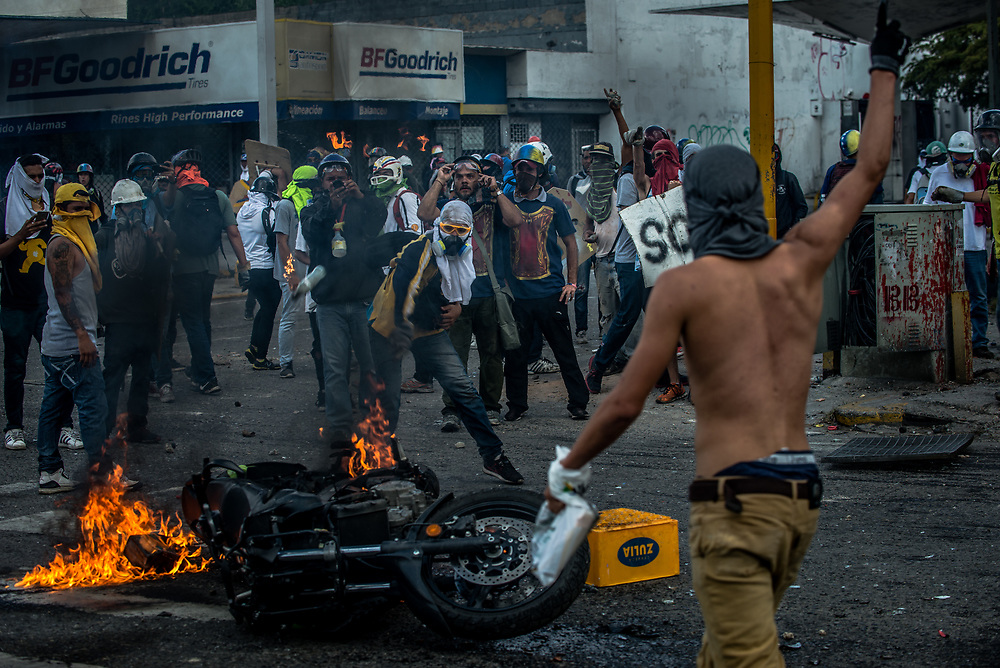 CARACAS, VENEZUELA - MAY 26, 2017:  Anti-government protesters burn a police motorcycle that they confiscated during clashes with government security forces. The streets of Caracas and other cities across Venezuela have been filled with tens of thousands of demonstrators for nearly 100 days of massive protests, held since April 1st. Protesters are enraged at the government for becoming an increasingly repressive, authoritarian regime that has delayed elections, used armed government loyalist to threaten dissidents, called for the Constitution to be re-written to favor them, jailed and tortured protesters and members of the political opposition, and whose corruption and failed economic policy has caused the current economic crisis that has led to widespread food and medicine shortages across the country.  Independent local media report nearly 100 people have been killed during protests and protest-related riots and looting.  The government currently only officially reports 75 deaths.  Over 2,000 people have been injured, and over 3,000 protesters have been detained by authorities.  PHOTO: Meridith Kohut