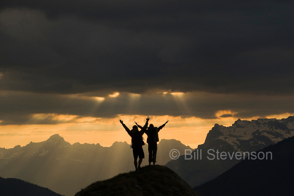 A picture of a couple raising their arms in joy on a mountain top looking at sun beams in the French Alps near Chamonix