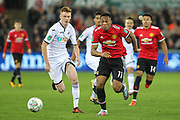 Anthony Martial of Manchester United breaks away from Sam Clucas of Swansea City during the EFL Cup match between Swansea City and Manchester United at the Liberty Stadium, Swansea, Wales on 24 October 2017. Photo by Andrew Lewis.