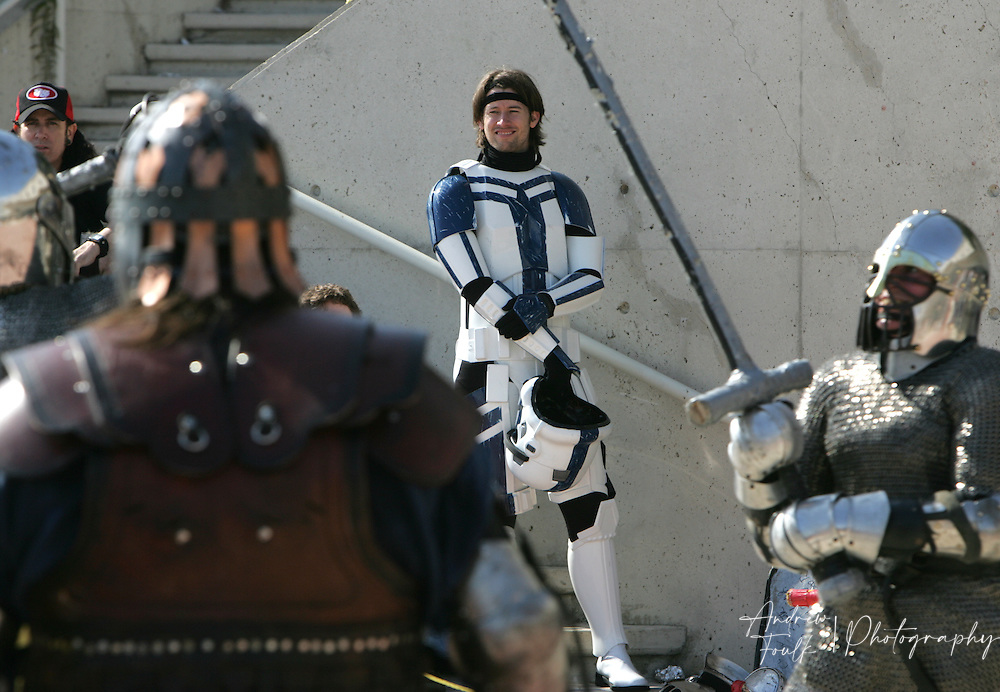 "Andrew Foulk/ Zuma Press.July 24, 2009, San Diego, California, USA. Comic Con.A lone "" Storm Trooper""  watches as a group of renaissance re-enactors do battle out side the San Diego convention center , during day two of the 40th annual San Diego International Comic Con."