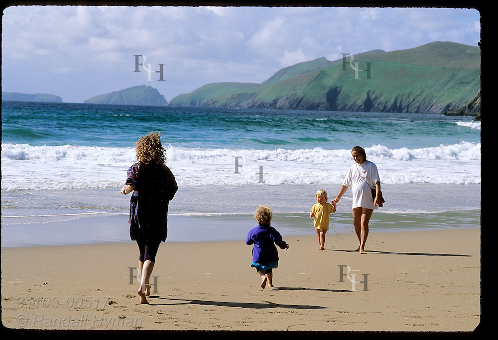 Moms & daughters frolic by the chilly North Atlantic waters of Coumeenole Beach; Dunmore Head & Blasket Islands afar; Dingle, Ireland.