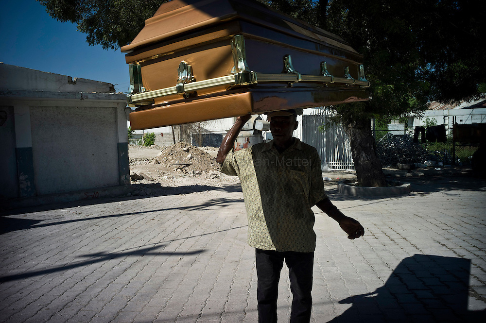 Ten days before the presidential elections, Port-au-Prince continues to be affected by the cholera epidemic, the number of victims still increasing in the capital./// A man carries a coffin, at the general hospital's morgue in Port-au-Prince.