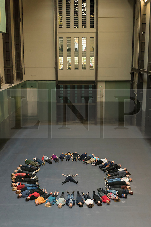 """© Licensed to London News Pictures. 01/10/2018. LONDON, UK. Tania Bruguera (centre) and volunteers prepare to create body impressions on the heat-sensitive floor. Unveiling of the this year's Hyundai Commission by Cuban artist and activist Tania Bruguera at Tate Modern.  The work is called """"an ever-increasing figure"""", which represents the scale of mass migration and the risks involved.  Visitors are invited to interact with the work which comprises a heat-sensitive floor, which includes a portrait of a person's face beneath, combined with low frequency sounds.  The work is on display 2 October to 24 February 2019..  Photo credit: Stephen Chung/LNP"""