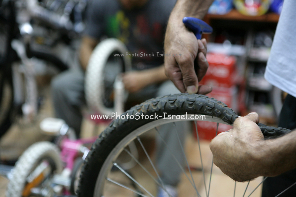 Israel, Tel Aviv, Bicycle shop. Man fixes a bike