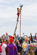 A costumed reveler places a chicken on the top of a greased pole during the Faquetigue Courir de Mardi Gras chicken run on Fat Tuesday February 17, 2015 in Eunice, Louisiana. The traditional Cajun Mardi Gras involves costumed revelers competing to catch a live chicken as they move from house to house throughout the rural community.