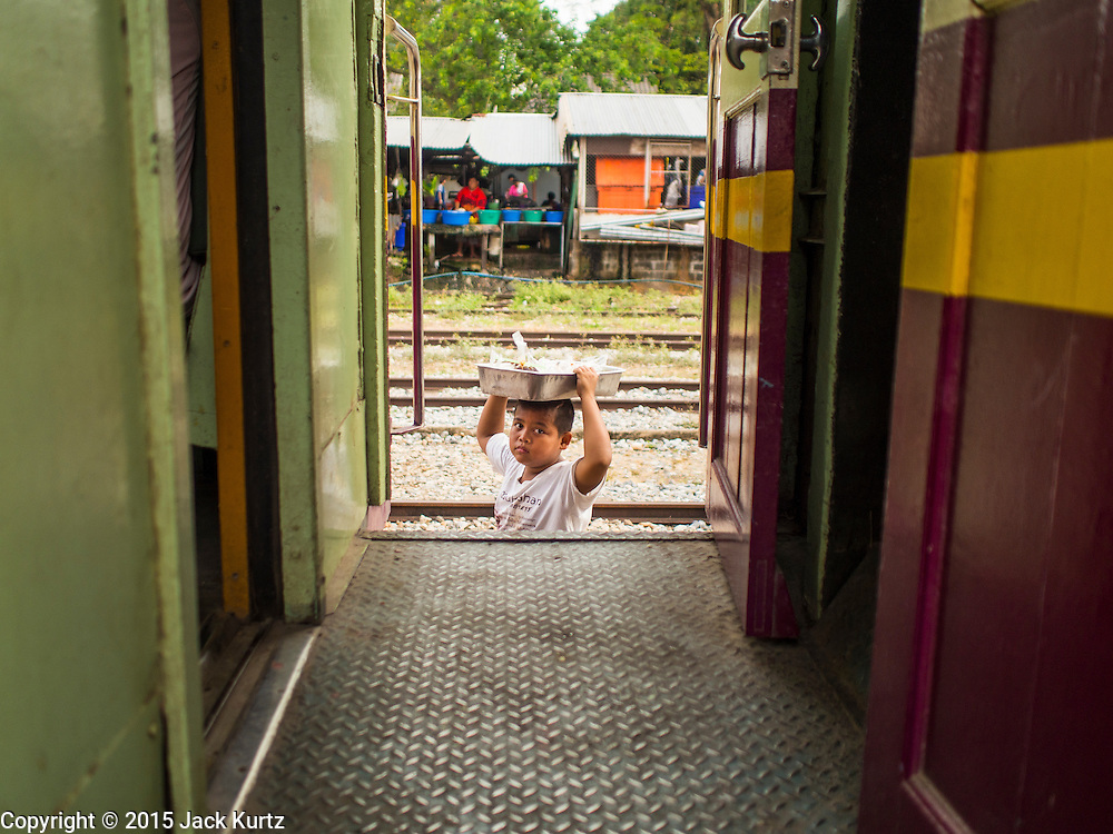 20 MARCH 2015 - KABIN BURI, PRACHINBURI, THAILAND: A child working as a vendor walks between cars in the Prachinburi train station. He was selling snacks to passengers riding a 3rd class train to Kabin Buri. The State Railways of Thailand (SRT), established in 1890, operates 4,043 kilometers of meter gauge track that reaches most parts of Thailand. Much of the track and many of the trains are poorly maintained and trains frequently run late. Accidents and mishaps are also commonplace. Successive governments, including the current military government, have promised to upgrade rail services. The military government has signed contracts with China to upgrade rail lines and bring high speed rail to Thailand. Japan has also expressed an interest in working on the Thai train system. Third class train travel is very inexpensive. Many lines are free for Thai citizens and even lines that aren't free are only a few Baht. Many third class tickets are under the equivalent of a dollar. Third class cars are not air-conditioned.   PHOTO BY JACK KURTZ