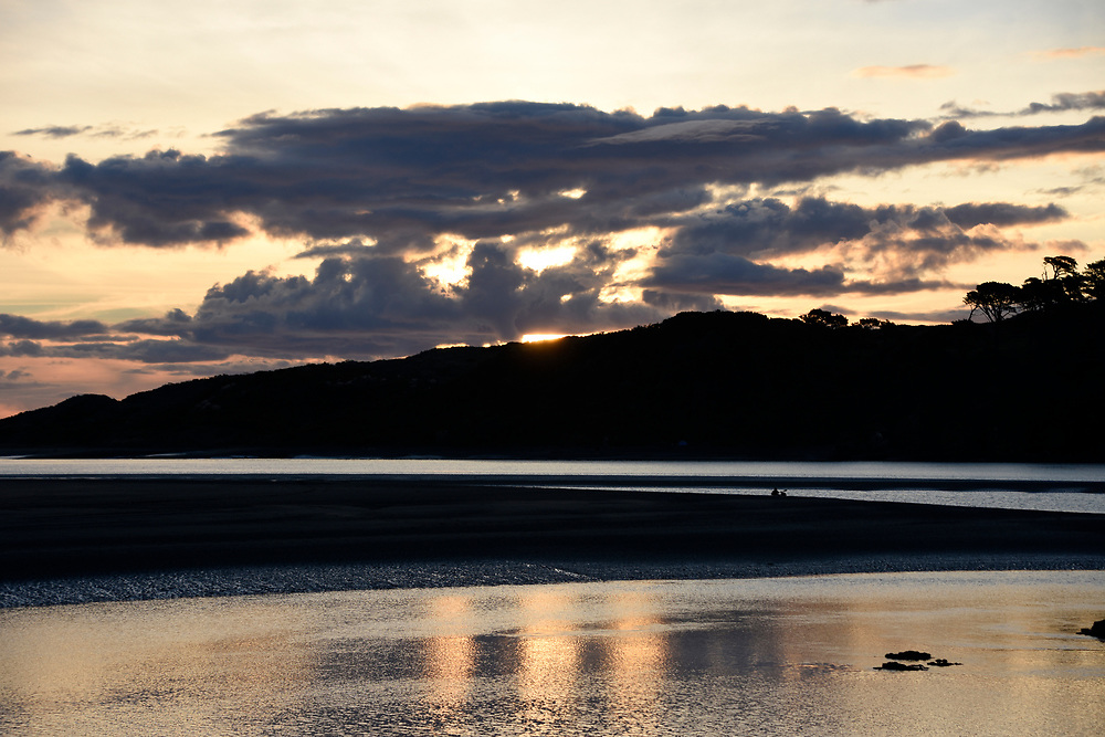 Sunset over the Raglan waters with people on the sands