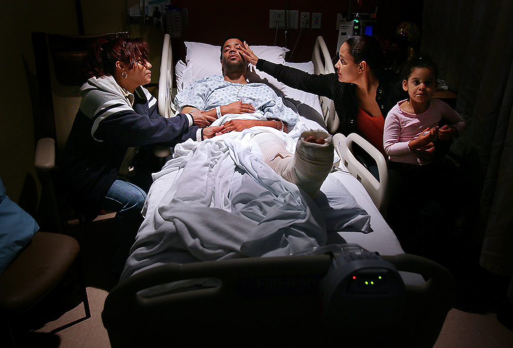 (060407 Boston, MA)  From left, Druselita Minaya, of Easton, mother of Jeffrey, and his sister Lissette Pagan, 31, of Easton, with her daughter Klarimar, 3, look over Jeffrey Cornielle, 28, as he recovers in his hospital bed at Boston Medical Center.   Jeffrey was, along with a female companion, a victim of a hit and run accident on route 128 after which no one came to his aid for approximately 4 hours.
