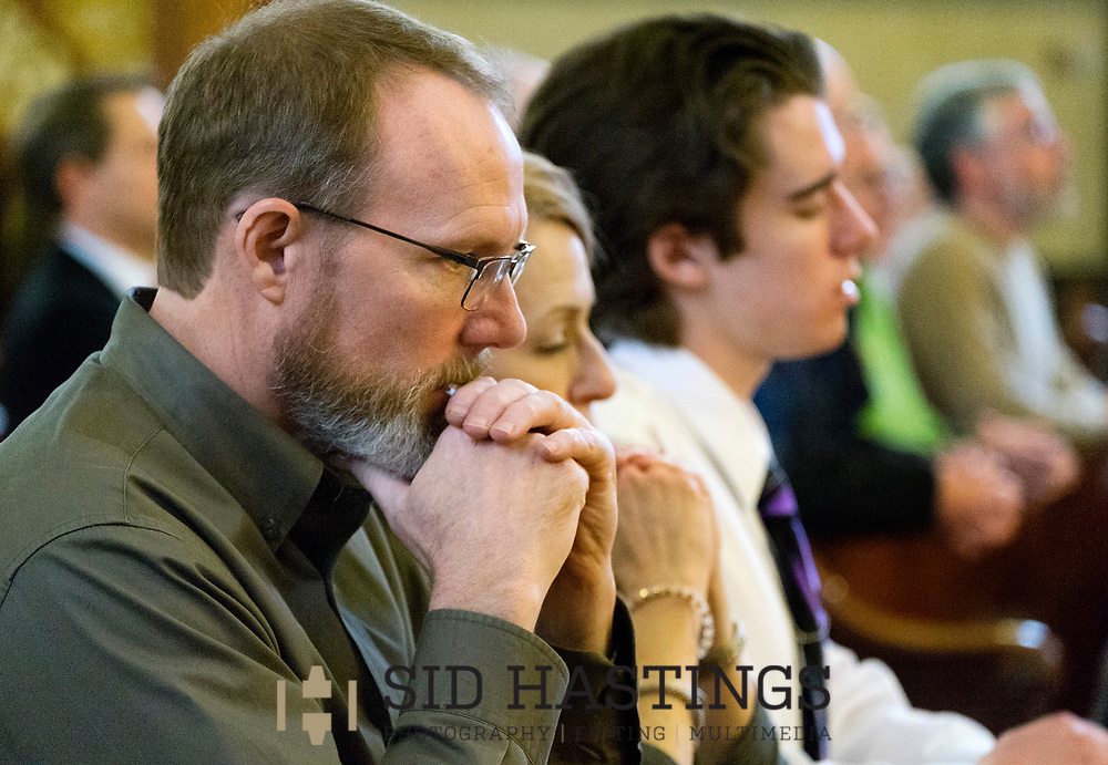 11 MARCH 2018 -- ST. LOUIS -- Dave Niehaus (left), a descendant of German immigrant Ignatius Strecker, joins his wife Chris Niehaus and sone Brian Niehaus during Mass at the Shrine of St. Joseph Sunday, March 11, 2018 in the Columbus Square neighborhood of St. Louis. Niehaus and other Strecker descendants gathered to remember the healing of the Strecker, thought mortally ill, during an 1864 service honoring Jesuit priest Peter Claver, a missionary who worked among slaves in South America during the 17th century. Strecker's healing was among the miracles attributed to Claver that led to his 1888 canonization by Pope Leo XIII. Photo © copyright 2018 Sid Hastings.