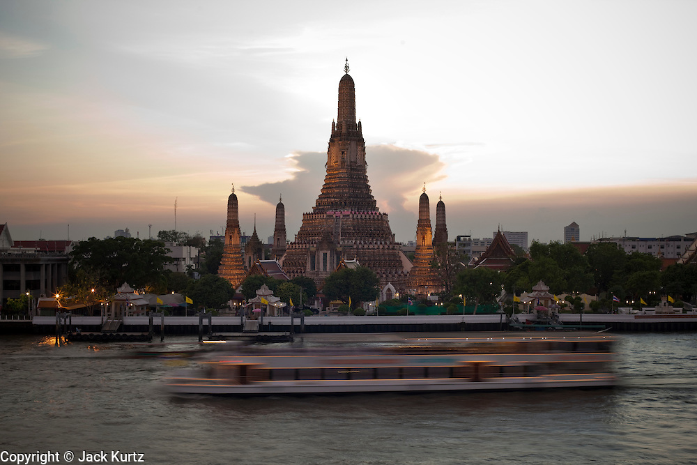 """07 MARCH 2009 -- BANGKOK, THAILAND: A sunset cruise passes Wat Arun, a Buddhist temple (wat) in the Bangkok Yai district of Bangkok, Thailand, on the west bank of the Chao Phraya River. The full name of the temple is Wat Arunratchawararam Ratchaworamahavihara. The outstanding feature of Wat Arun is its central prang (Khmer-style tower). It may be named """"Temple of the Dawn"""" because the first light of morning reflects off the surface of the temple with a pearly iridescence. Steep steps lead to the two terraces. The height is reported by different sources as between 66,80 m and 86 m. The corners are surrounded by 4 smaller satellite prangs. The prangs are decorated by seashells and bits of porcelain which had previously been used as ballast by boats coming to Bangkok from China. The central prang is topped with a seven-pronged trident, referred to by many sources as the """"trident of Shiva"""". Around the base of the prangs are various figures of ancient Chinese soldiers and animals. Over the second terrace are four statues of the Hindu god Indra riding on Erawan. The temple was built in the days of Thailand's ancient capital of Ayutthaya and originally known as Wat Makok (The Olive Temple). In the ensuing era when Thonburi was capital, King Taksin changed the name to Wat Chaeng. The later King Rama II. changed the name to Wat Arunratchatharam. He restored the temple and enlarged the central prang. The work was finished by King Rama III. King Rama IV gave the temple the present name Wat Arunratchawararam. As a sign of changing times, Wat Arun officially ordained its first westerner, an American, in 2005. The central prang symbolizes Mount Meru of the Indian cosmology. The satellite prangs are devoted to the wind god Phra Phai. Photo By Jack Kurtz"""
