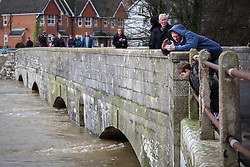 © Licensed to London News Pictures. 03/01/2014. Christchurch, Dorset, UK. A man taking a photo of the flood water flowing under the Iford Bridge on the River Stour in Christchurch, Dorset, UK on a day that will bring the risk of flooding to much of the south west of England & Wales. A severe weather warning has been issued by the Environment Agency for the area. Photo credit : Rob Arnold/LNP
