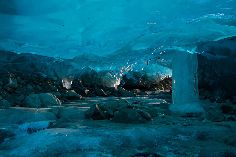 A frozen pillar of ice flows down from the ceiling of an ice cave beneath the Mendenhall Glacier.