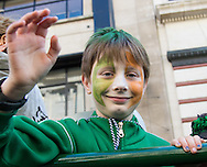 His face painted in the colours of the Irish flag a boy waves to spectators during the St Patrick's Day Parade in Westminster, London.<br /> Picture by Paul Davey/Focus Images Ltd +447966 016296<br /> 13/03/2016