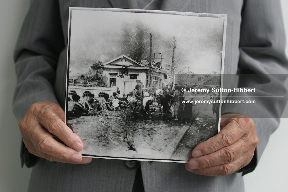 Sunao Tsuboi holds a photograph, by photographer Yoshito Matsushige, taken on Miyuki Bridge 3 hours after the atomic bombing of Hiroshima. This was the first photo taken after the bombing, and shows Sunao Tsuboi sitting injured on the bridge. Hiroshima, Japan, 21.07.2005
