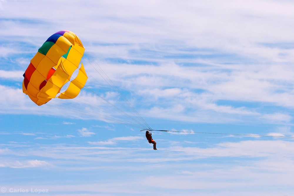 A woman is doing  parasailing as part of the fun activities of her vacations in the city of Ixtapa in Mexico.