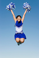 Smiling Cheerleader jumping in mid-air (portrait) (low angle view)