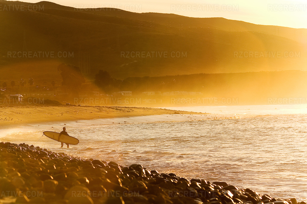 A surfer enters the water at sunrise near San Onofre. Photo by Robert Zaleski/rzcreative.com