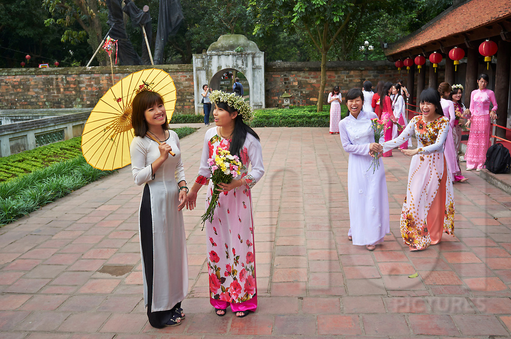 Young Vietnamese girls wearing the traditional Ao Dai outfit meet at the Temple of Literature for a photo shoot, Hanoi, Vietnam, Southeast Asia