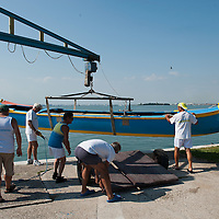 "VENICE, ITALY - SEPTEMBER 04:  Members of the Voga Veneta Lido rowing club launch a ""Caorlina"" a traditional Venetian boat using a boat crane ahead of Sunday Historic Regata on September 4, 2010 in Venice, Italy. The Historic Regata is the most exciting rowing race on the Gran Canal for the locals and one of the most spectacular ***Agreed Fee's Apply To All Image Use***.Marco Secchi /Xianpix. tel +44 (0) 207 1939846. e-mail ms@msecchi.com .www.marcosecchi.com"