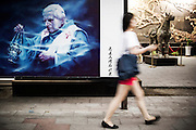 A Chinese woman walks past a drawing of Pope Benedict XVI Joseph Ratzinger in the streets of 798 Art District in Beijing, China, July 19, 2014.<br /> <br /> 798 Art District (Chinese: 798艺术区; pinyin: 798 Yìshùqū), or Dashanzi Art District, is a 50-year old decommissioned military factory buildings with unique architectural style. Located in Chaoyang District of Beijing, that houses a thriving artistic community. Since the beginning of 2000, 798 has become a centre for art galleries, artists's ateliers and contemporary arts exhibitions. The buildings are within alleys number 2 and 4 on Jiǔxiānqiáo Lù (酒仙桥路), south of the Dàshānziqiáo flyover (大山子桥). <br /> <br /> © Giorgio Perottino