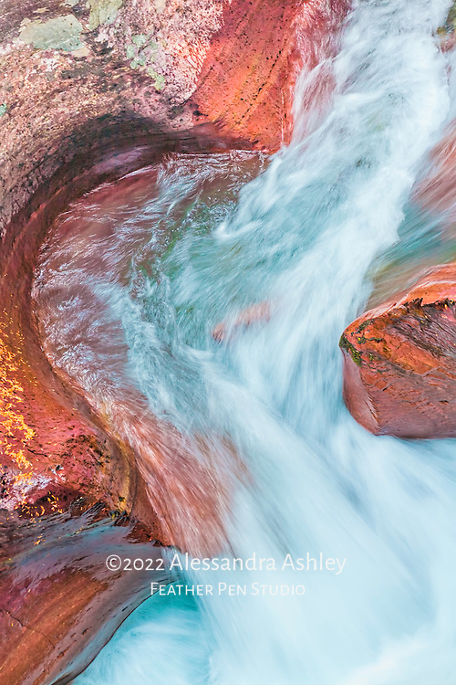 Glacial blue water rushes through striated rock formations at Avalanche Gorge, Glacier National Park.