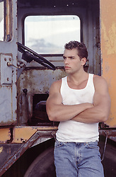 hot man in a tank top leaning against a truck