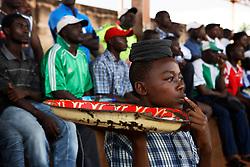 A boy selling peanuts watches the game..Coup de Cameroon Quarter final between Union Sportif de Douala (green and white) and Canon de Yaounde (red and green) at the military stadium in central Yaounde. Yaounde, Cameroon.