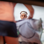PARIS, FRANCE June 04. Roger Federer of Switzerland requests his towel from a ball girl during his match against Stan Wawrinka of Switzerland on Court Suzanne Lenglen during the Men's Singles Quarter Final match at the 2019 French Open Tennis Tournament at Roland Garros on June 4th 2019 in Paris, France. (Photo by Tim Clayton/Corbis via Getty Images)