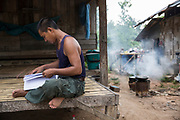 Supot Kalasong, 42, sits and read official documents ready to submit to the Government outside his house in Klong Sai Pattana. Mr Supot was shot in April 2016.<br /> <br /> Since 2008, this community of around 70 families have been embroiled in a conflict with a palm oil company that locals allege has been trying to violently evict them. Since 2010, four members of the community have been shot dead and a fifth shot, but survived.<br /> <br /> For decades the palm oil company Jiew Kang Jue Pattana Co., Ltd has illegally occupied and cultivated palm oil trees on a 535-acre plot of land in the Chai Buri District of Surat Thani Province. <br /> <br /> The company operated with no official legal documentation or land concession, until the Southern Peasant's Federation of Thailand (SPFT), who supports the community, began investigating them and collecting evidence.<br /> <br /> This evidence ultimately lead to a Supreme Court ruling against the company for illegal trespassing and land encroachment. But the community still struggles to remain on the land to this day with the last shooting happening in April 2016, years after the court case was won.