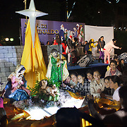 A group of Filipino women take photographs of each others with a Christmas statue of the new born Christ, Maria and Joseph. It is Christmas Eve and thousands of Catholic Filipino women have congregated in Central Hong Kong to celebrate Christmas. Hong Kong has a huge Filipino population, most of them women working as domestic servants. They meet in public on their days off since none of them have their own private accomodation. 7 million people live on 1,104km square, making it Hong Kong the most vertical city in the world.