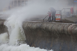 © Licensed to London News Pictures. 21/10/2017. Southsea, UK.  A man and child get soaked as they get close to the large waves crashing against the promenade in Southsea today, 21st October 2017. Storm Brian has brought strong winds and large waves to the UK coast. Photo credit: Rob Arnold/LNP