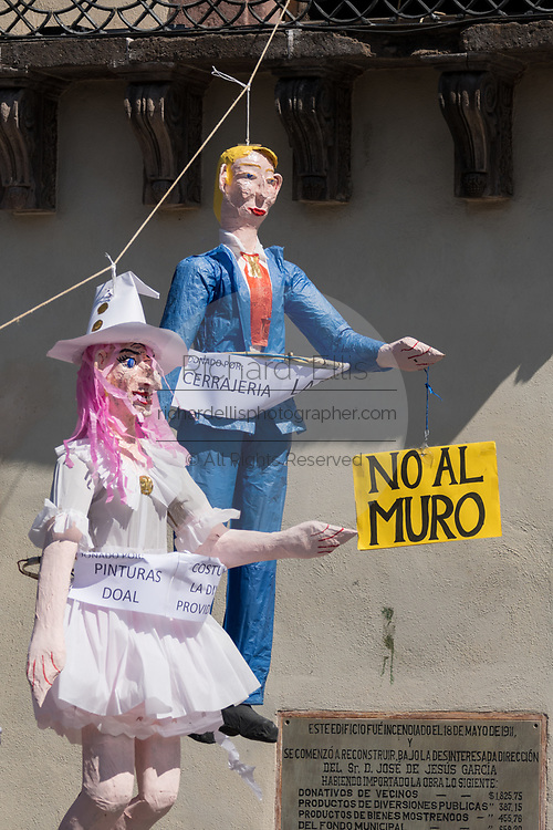 "An effigy of U.S. President Donald Trump hangs in the Plaza Allende with other paper dolls in preparation for the Burning of Judas Easter-time ritual marking the end of Holy Week April 1, 2018 in San Miguel de Allende, Mexico. While the tradition includes burning a paper effigy of Judas a recent popular addition has been paper doll caricatures of Donald Trump across Mexico. The doll is holding a sign saying ""No Wall"" in reference to the Trump border wall."