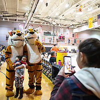 Lilianna Gonzales, 14, takes a photo of her siblings Ofelia Gonzales, 7, and Christopher Trujillo, 11 months posing with the Gallup Bengal mascots at the Lady Bengals and Lady Patriots basketball game Wednesday night at Gallup High School.