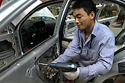 A production line worker builds the door of a Volkswagen Jetta, on the assembley line at the China First Auto Works (FAW) plant in Changchun, China May 25, 2004. First Automotive Works (FAW), China's largest vehicle maker and partner of Volkswagen, is interested in listing abroad within the next five years.