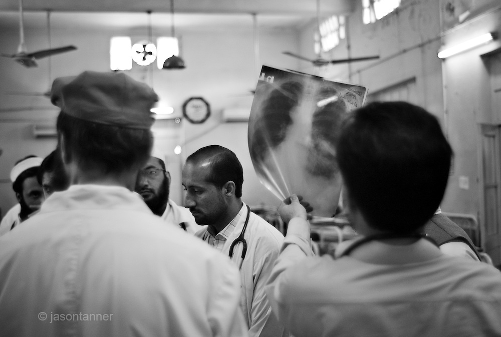 A doctor gives consultation to a patient suspected of having Tuberculosis on a ward in the Department of Pulmonary Diseases at Lady Reading Hospital in Peshawar.....Patients admitted for treatment range from teenagers to the elderly. The hosiptal has a policy of non-isolation. Patients can lead normal lives and do not be isolated. According to chest specialist Dr Shahzada Athat, patients already bear the burden of social stigma that people create around a patient suffering with TB. They advocate treatment, which can be provided at home...The hospital follows the DOTS (Directly Observed Treatment Courses) policy directive issued from World Health Organisation (WHO) where a person of social standing or responsibility (teacher or health worker) observes the administration of medicines by the patient...Following an intensive phase of initial therapy and further eight months of treatment, the patient becomes non-infectious. Patient care at the hospital is free courtesy of government funding..