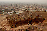 Boys race up Dala Hill, which overlooks Kano's Old City, to play just after sunrise. Kano, the epicenter of the world's largest concentration of polio cases, is covered with red dust during Nigeria's dry season, which stretches from November to late April.