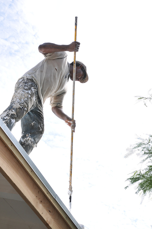 Time to finish the job! A Crest Construction worker applies the final coat of elastomeric coating to my roof.