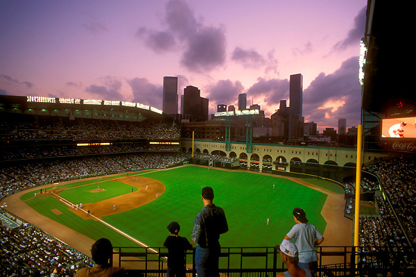 Stock photo of a man and children watching a game under the stadium's open roof, showing Houston's skyline at dusk