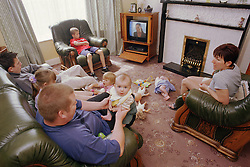 Family sitting together in front room watching television,
