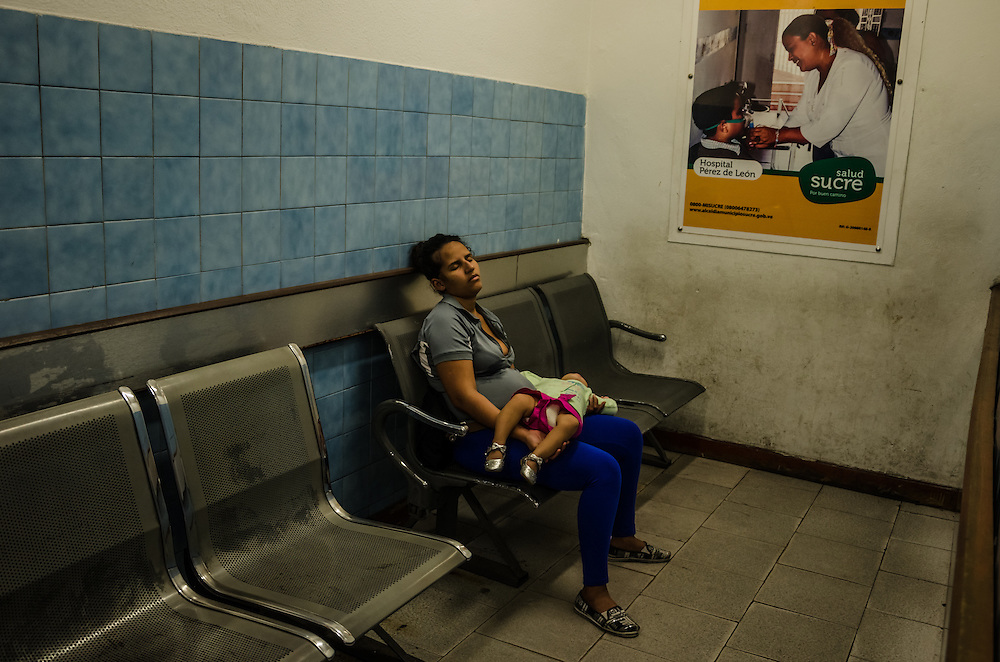 CARACAS, VENEZUELA - JANUARY 21, 2015: An exhausted mother waits with her daughter to be admitted to the pediatric emergency room of the state hospital in the Petare slum in Caracas. Doctors here say they are working with a bare minimum of supplies, and often have to turn patients away. Despite being a petro-state with one of the largest oil reserves in the world, basic and advanced medical supplies from gauze and surgical gloves, to heart stints, are difficult to find in hospitals and pharmacies across Venezuela.