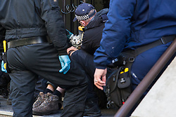 London, UK. 17 October, 2019. Metropolitan Police officers work to extract and arrest campaigners against the arms trade from Extinction Rebellion Scotland who had glued or locked themselves onto the entrance to the registered office of Lockheed Martin UK in protest against their profiting from arms sold for use in wars and in solidarity with the Kurdish people following the Turkish invasion of Kurdish-held areas of north-east Syria.