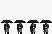 Businessmen holding umbrellas standing side by side