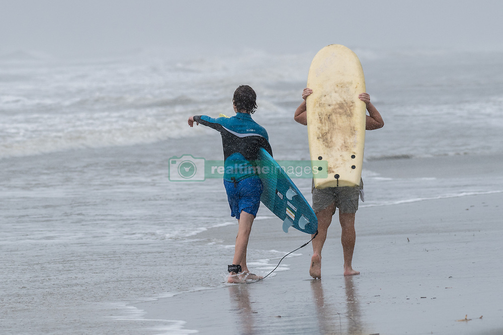 October 7, 2016 - Isle Of Palms, United States - Young surfers walk along the beach in driving rain and wind as Hurricane Matthew approaches the coast October 7, 2016 in Isle of Palms, South Carolina. The hurricane is expected to make landfall near Charleston as a Category 2 storm with strong winds, rain and storm serge. (Credit Image: © Richard Ellis via ZUMA Wire)