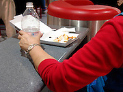 Close up of the arm and bottle at a fast food place.