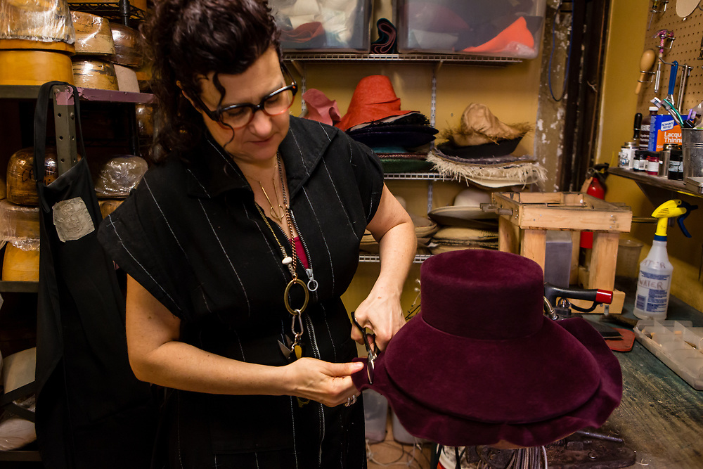 Trimming the excess from the brim of a felt hat. The hat bodies are oversized, to allow for varying crown heights and brim widths.