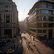 Three businessman walk over a junction in late afternoon sunlight across a street in the City of London, the heart of the capital's financial district.